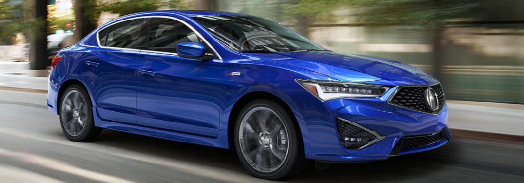 Front passenger angle of a blue 2020 Acura ILX driving down a road