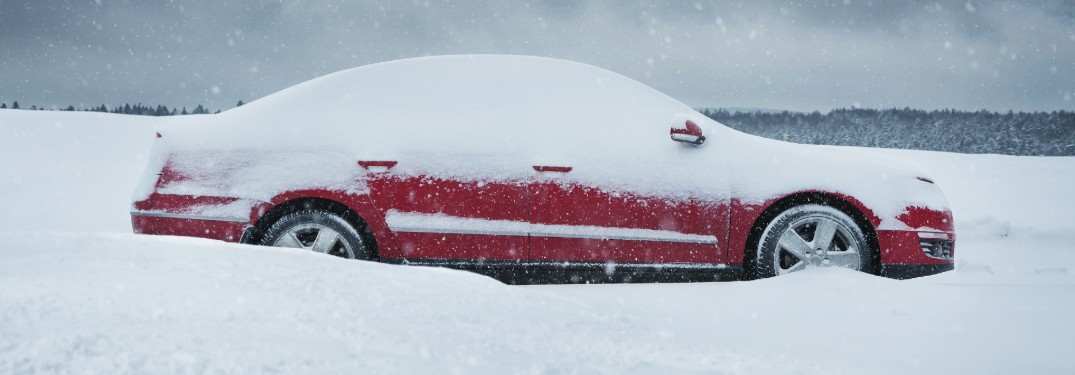 Passenger angle of a red car covered in heavy snow