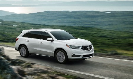 Front passenger angle of a white 2020 Acura MDX driving down a road