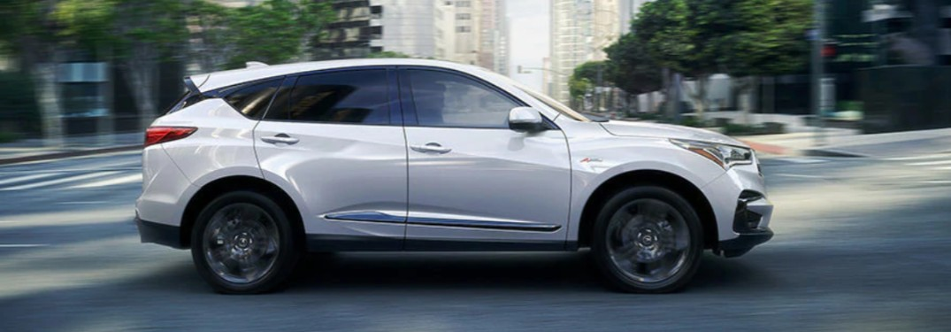 Passenger angle of a white 2020 Acura RDX driving down a city street