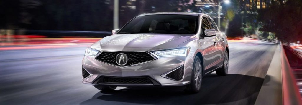 Front driver angle of a silver 2020 Acura ILX driving at night