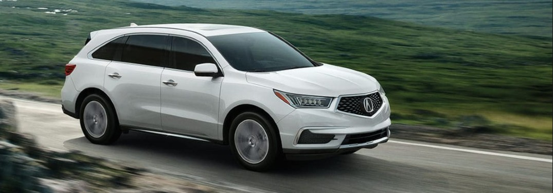 Front passenger angle of a white 2020 Acura MDX driving on a country road