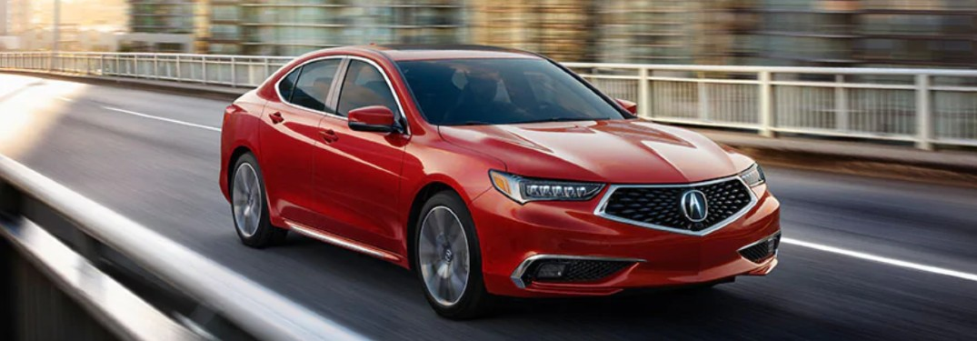 Front passenger angle of a red 2020 Acura TLX driving down a road