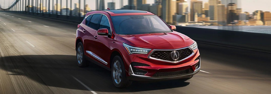 Front passenger angle of a red 2020 Acura RDX driving on a bridge