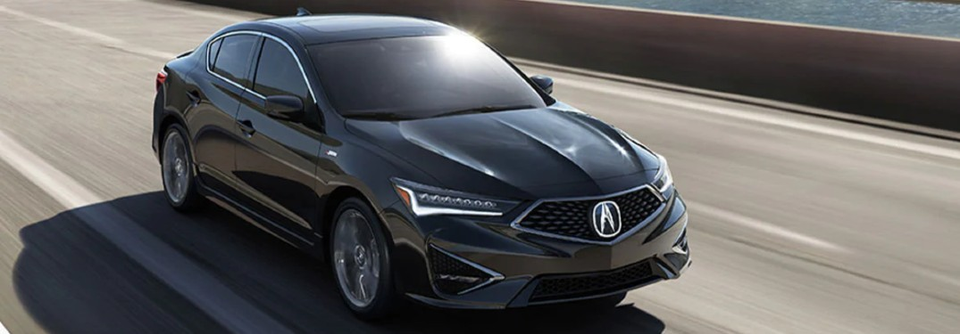 Front passenger angle of a black 2020 Acura ILX driving on a road