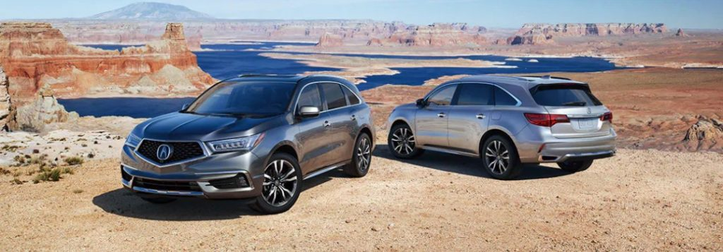 Two 2020 Acura MDX vehicles parked next to each other overlooking a canyon with water