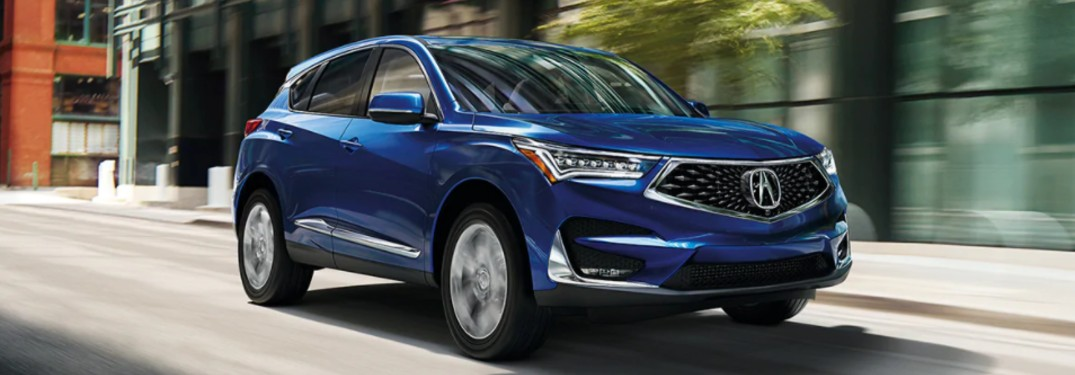 Front passenger angle of a blue 2021 Acura RDX driving down a road