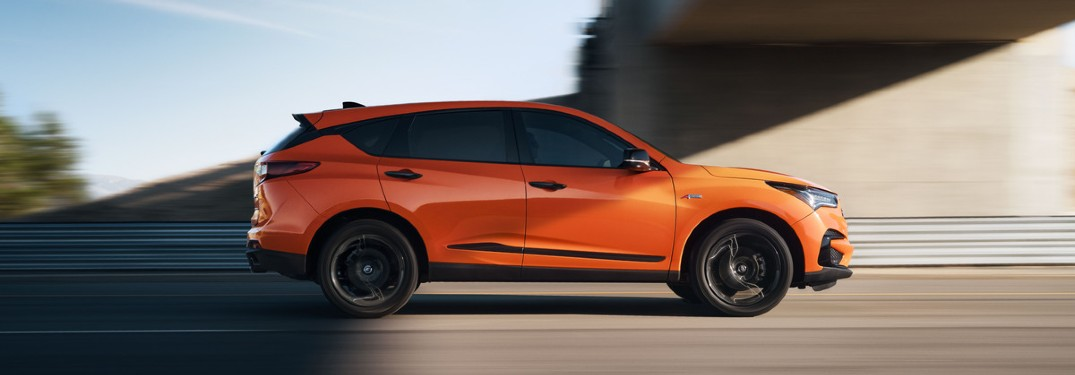 Passenger angle of an orange 2021 Acura RDX PMC Edition driving on a highway