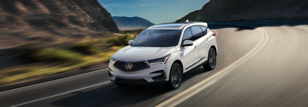 Front driver angle of a white 2021 Acura RDX driving on a road