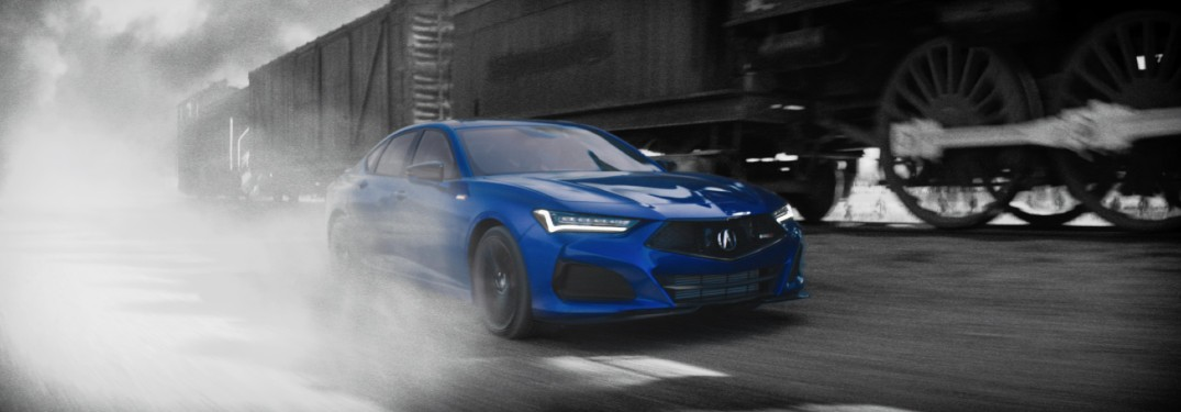 Blue 2021 Acura TLX driving by a train in black and white