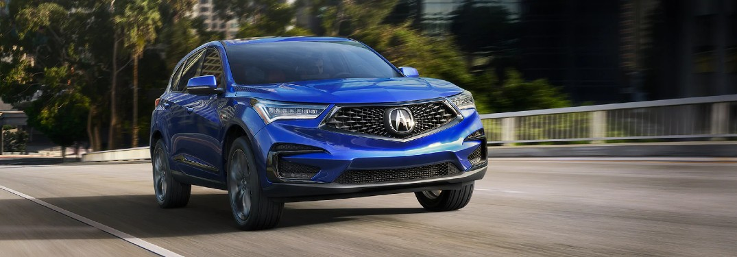 Front passenger angle of a blue 2021 Acura RDX driving on a road