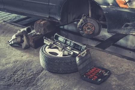 Brake rotor on a car with its tire on the ground by it