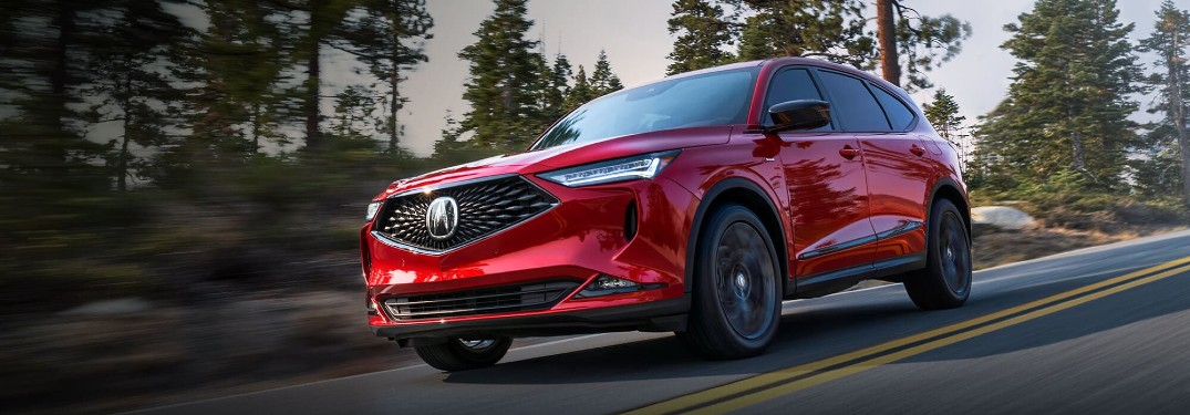 Front driver angle of a red 2022 Acura MDX driving on a road