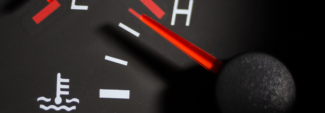 Close up of a temperature gauge spiking to the red inside a car