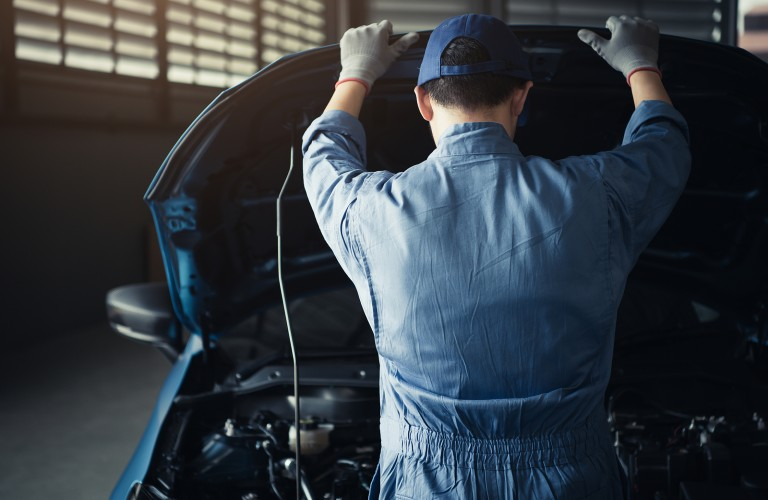 Mechanic opening the hood of a car