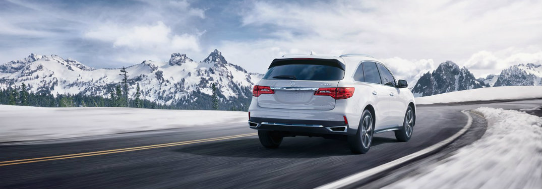 2018 Acura MDX driving by snowy mountains