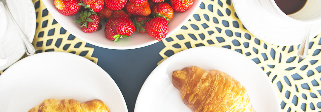 croissant and strawberry of food on dishes photographed from above