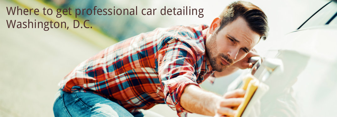 Handsome man in plaid shirt rubbing side body of car with yellow rag