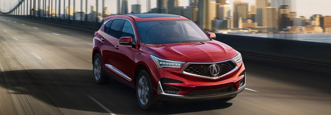 Front passenger angle of a red 2020 Acura RDX driving across a bridge