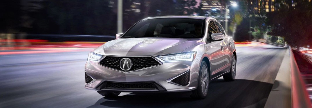Front driver angle of a silver 2019 Acura ILX driving through the city at night