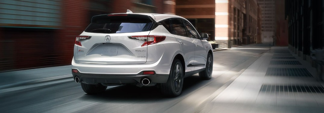 Rear passenger angle of a white 2020 Acura RDX driving down a street