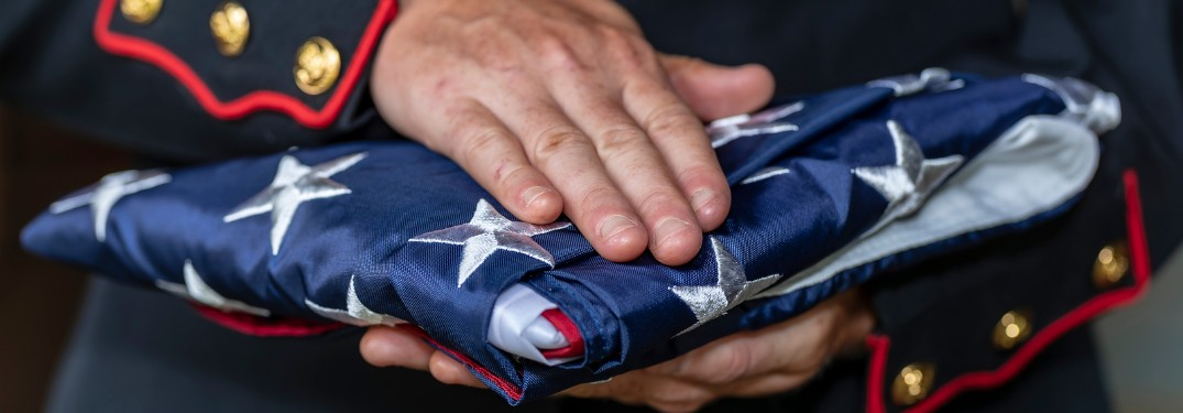 Close up of a Marine's hands holding a folded American flag