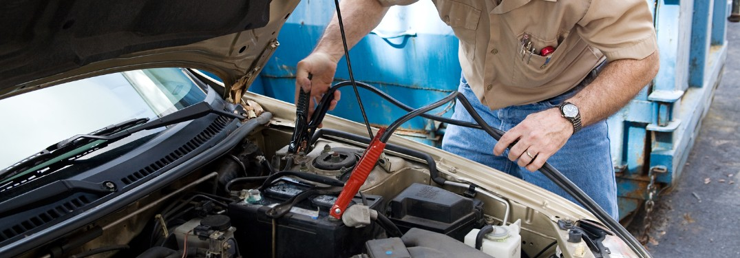 Mechanic using jumper cables on a battery in a car