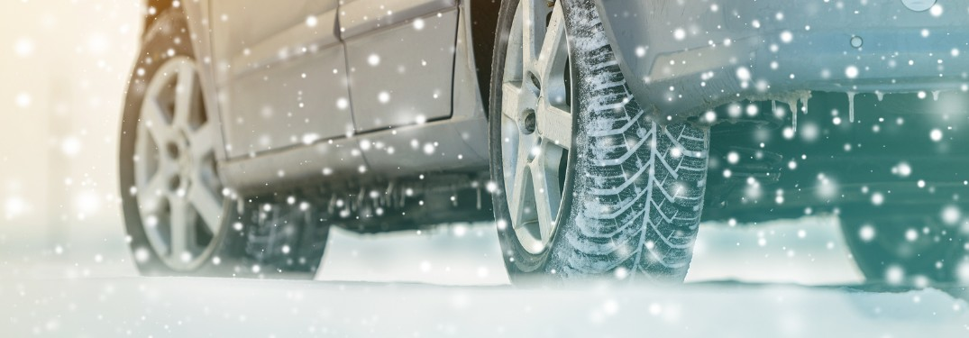 Close up of the tires of a car driving through deep snow
