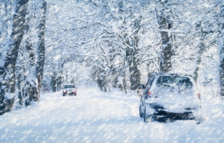 Rear angle of a car driving in heavy snow with another car driving towards it