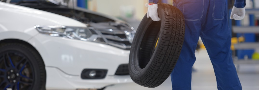 Mechanic holding a tire and facing a white car in the background