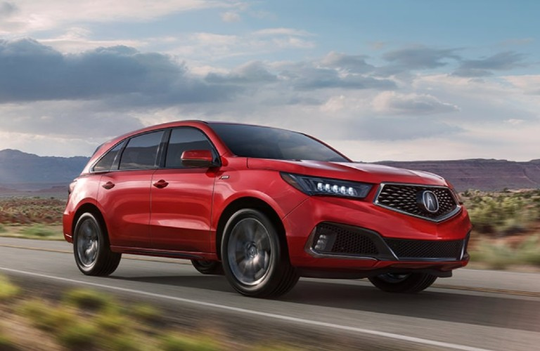 Front passenger angle of a red 2020 Acura MDX A-Spec Package driving on a road