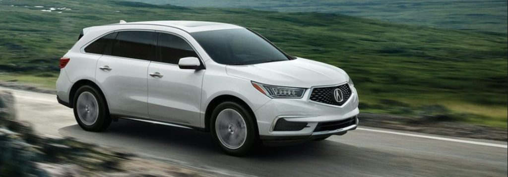 Front passenger angle of a white 2020 Acura MDX driving on a rural road