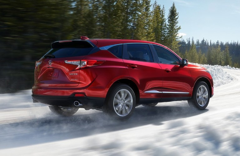 Rear passenger angle of a red 2020 Acura RDX driving on snow