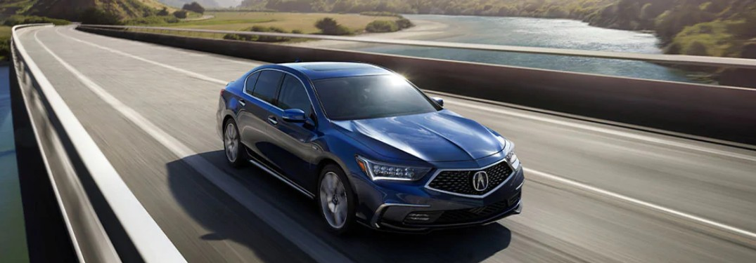 Front passenger angle of a blue 2020 Acura RLX driving on a bridge
