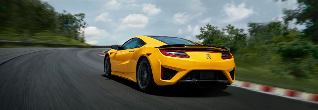 Rear driver angle of a yellow 2020 Acura NSX