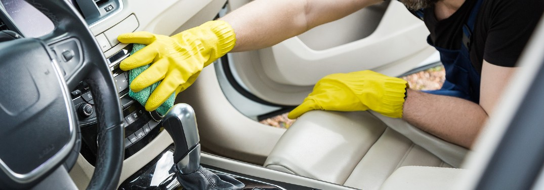Worker wearing gloves cleaning the interior of a car