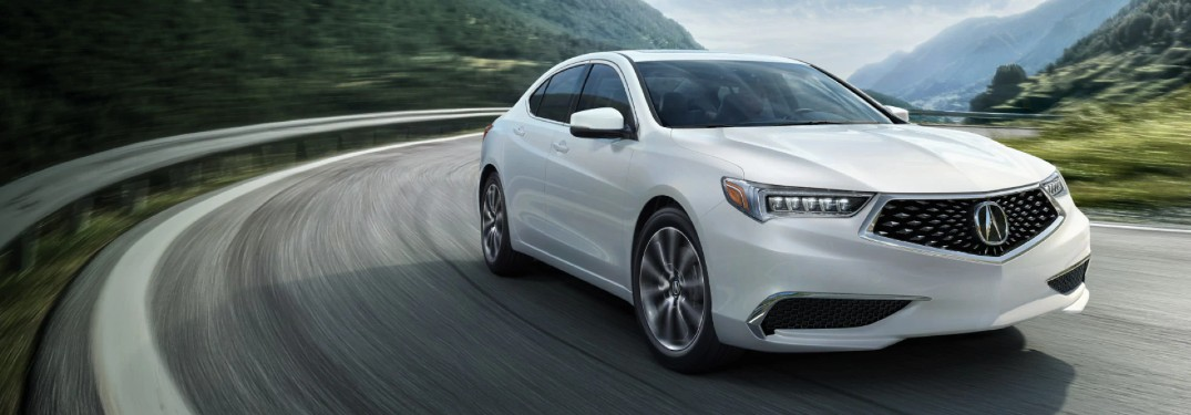 Front passenger angle of a white 2020 Acura TLX driving on a road