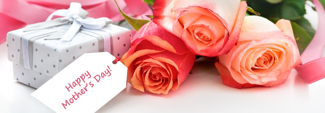 """Flowers and a gift with a tag that says """"Happy Mother's Day"""""""