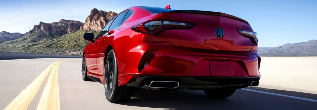 Rear driver angle of a red 2021 Acura TLX driving on a road