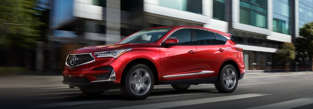 Front driver angle of a red 2021 Acura RDX driving in a city