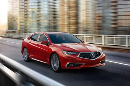 Front passenger angle of a red 2020 Acura TLX driving on a city street