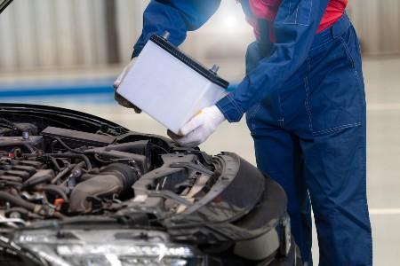 Mechanic replacing a car battery