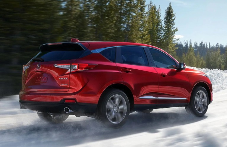 Rear passenger angle of a red 2021 Acura RDX driving in snow