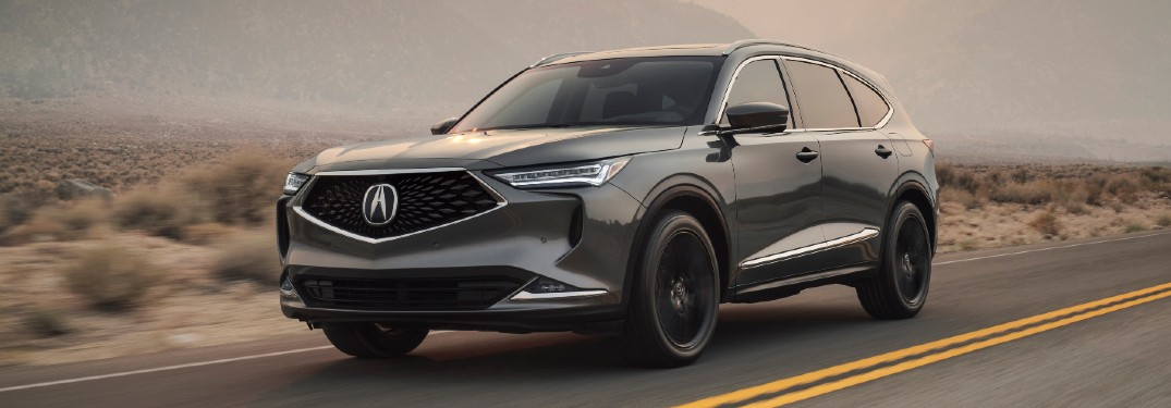 Front driver angle of a grey 2022 Acura MDX driving on a road
