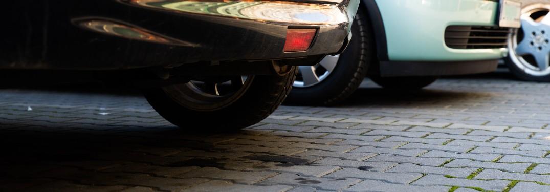 Oil spots on the ground underneath a car