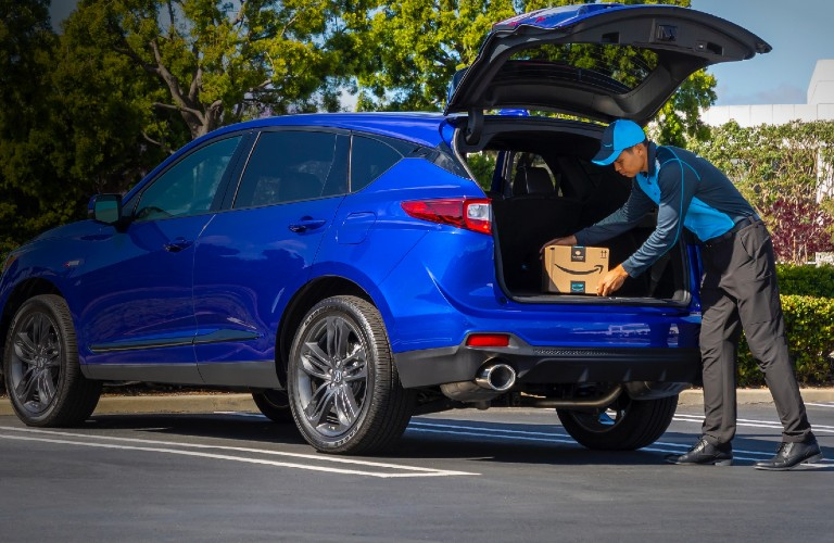 Rear driver angle of a blue 2021 Acura RDX with an Amazon worker putting a package in its cargo area