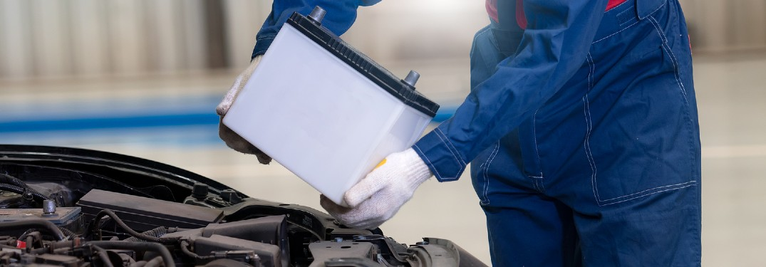 Mechanic replacing the battery in a car