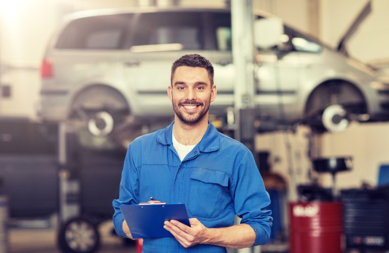 Happy mechanic inside a car auto shop