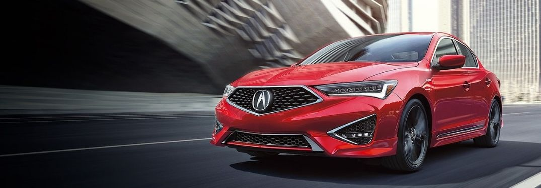 A red 2022 Acura ILX driving under a flyover.
