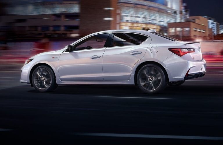 A 2022 Acura ILX driving on the city road at night.